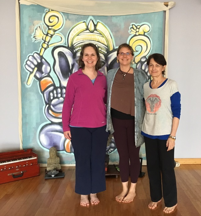 Photograph of three teachers in front of Ganesh banner at Sanctuary.